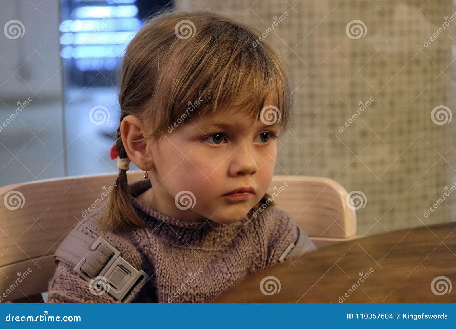 La pequeña muchacha linda sobre algo pensó