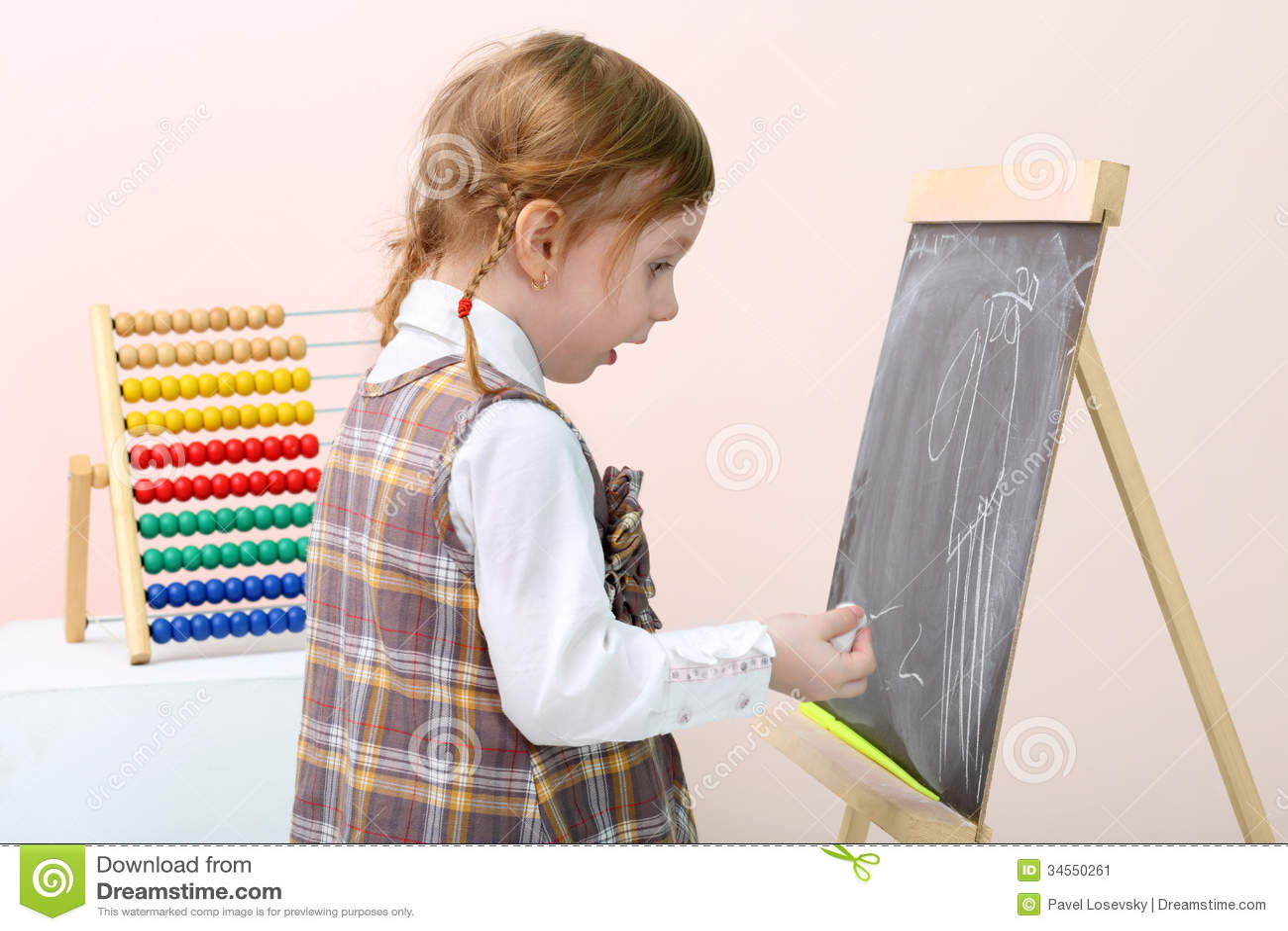 La pequeña muchacha sorprendida dibuja por la tiza en la pizarra