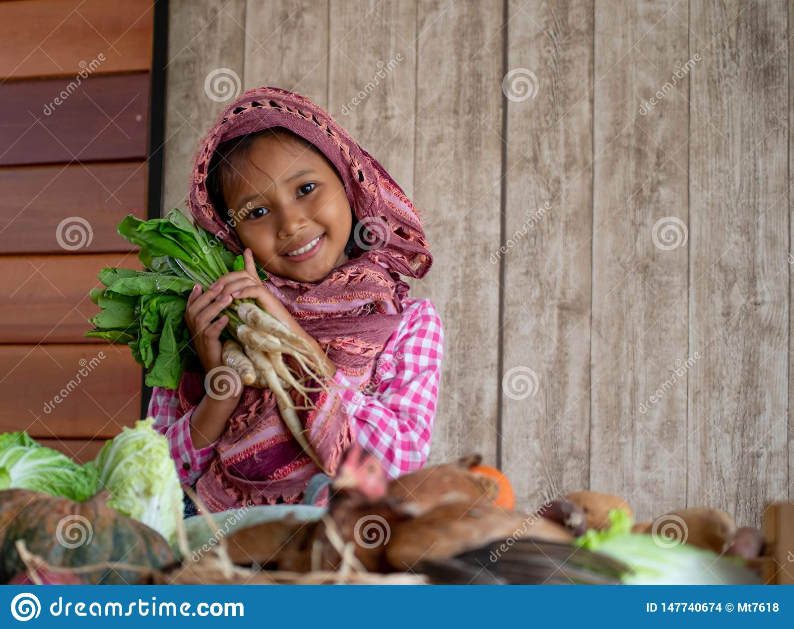La peque?a mirada asi?tica de la chica joven adelante y la sonrisa entre diversos tipos de verdura tambi?n celebran el r?bano det
