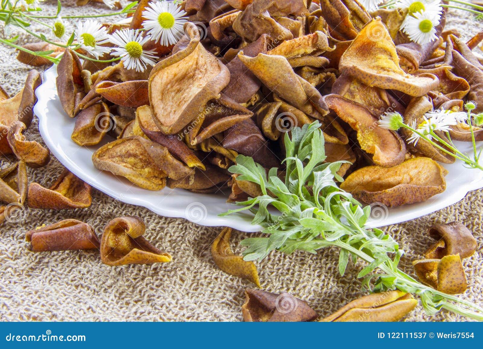La pera marrón secada corta la placa blanca con las flores blancas Las flores de la margarita blanca y un ajenjo verde ramifican