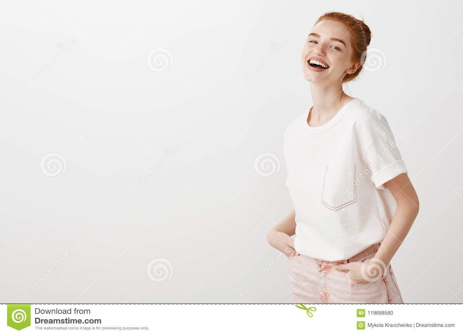 La persona amorosa mi incita sempre a ridere Ragazza alla moda dello zenzero in jeans d avanguardia e maglietta bianca, tenentesi