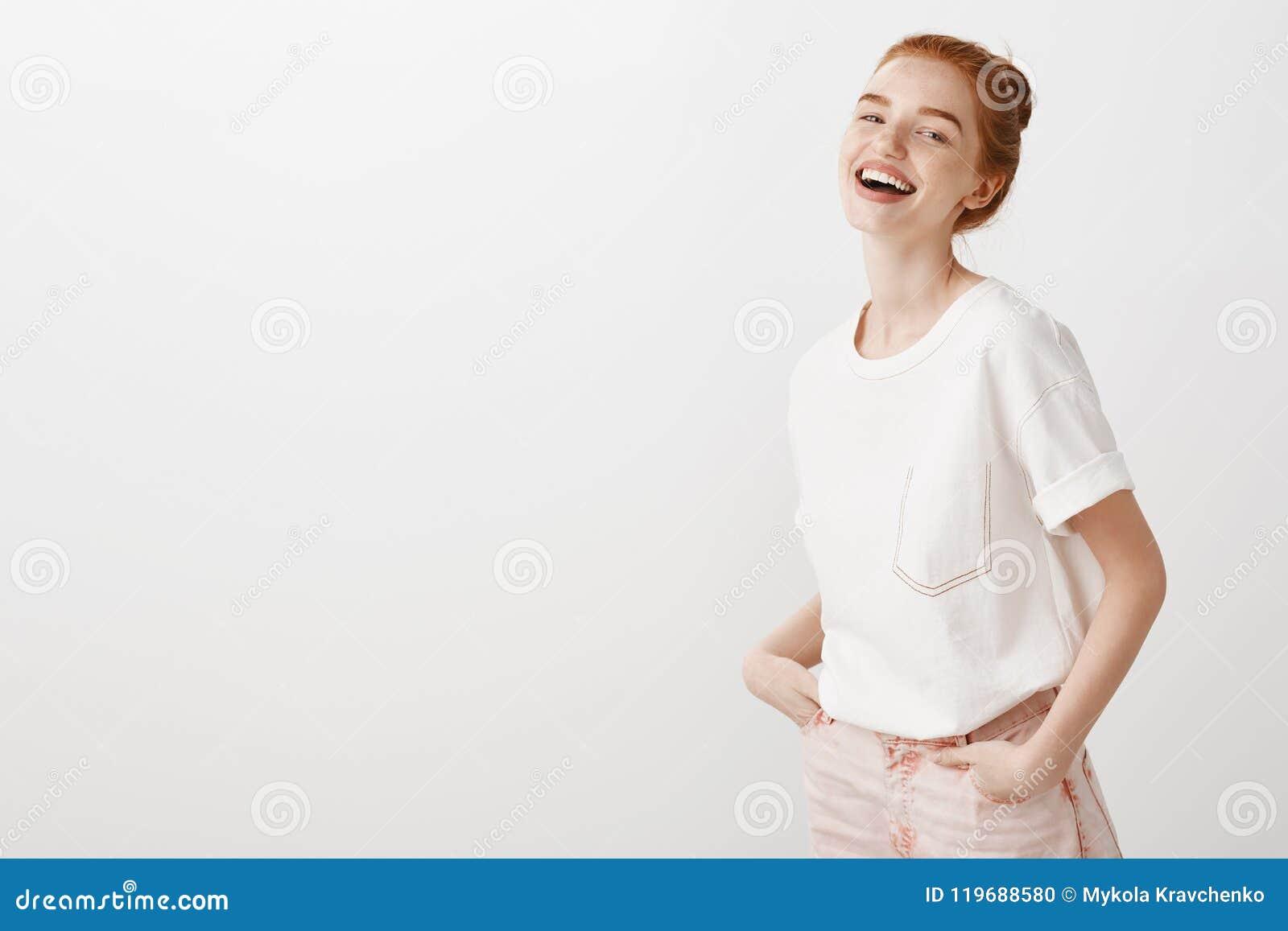 La persona cariñosa hace siempre que ríe Muchacha elegante del jengibre en vaqueros de moda y la camiseta blanca, llevando a cabo
