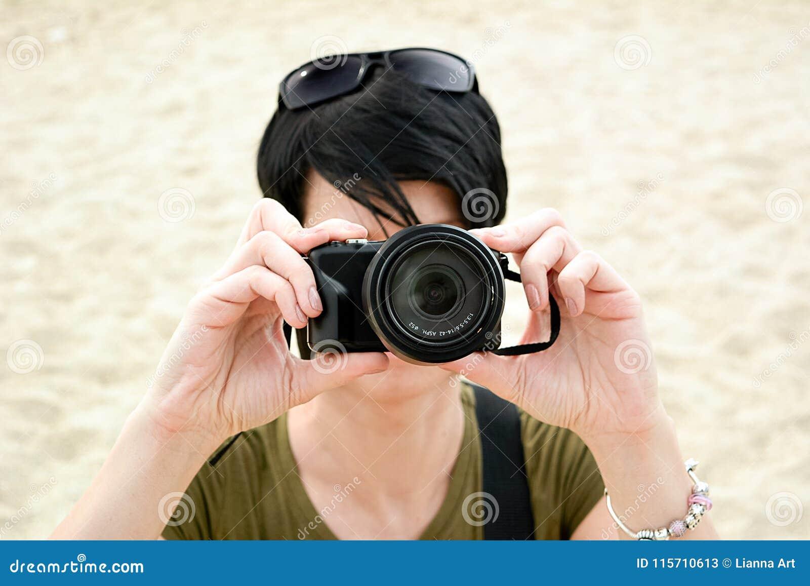 La persona con la piccola macchina fotografica nera