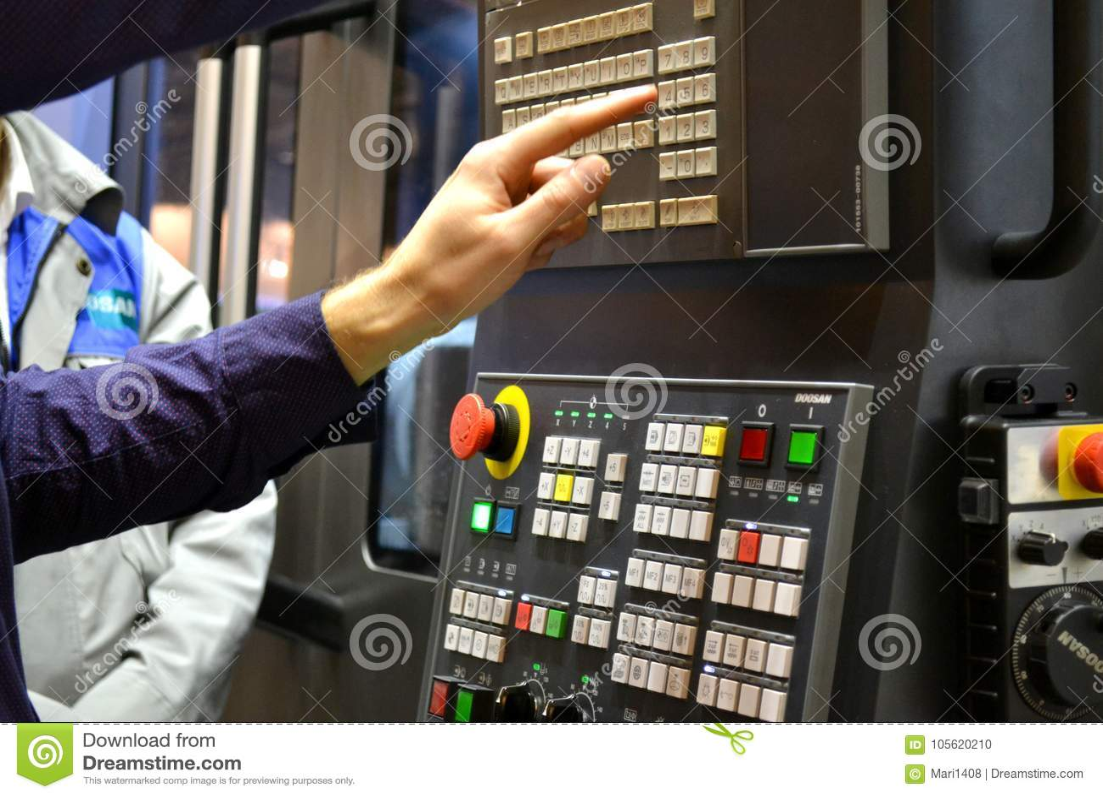 La persona lavora dietro il pannello di controllo della macchina di produzione