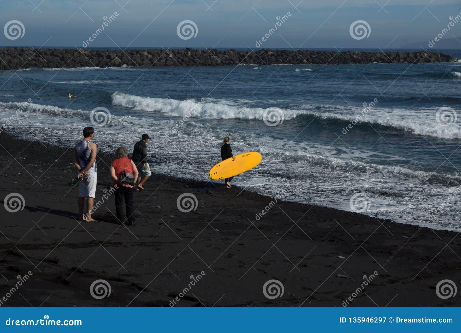 La persona que practica surf de la muchacha va al océano