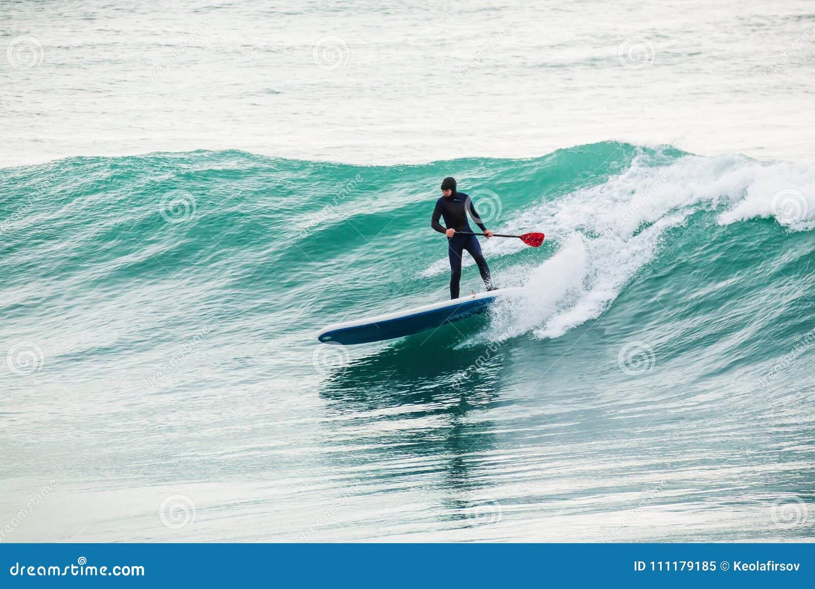 La persona que practica surf encendido se levanta el tablero de paleta en onda azul Invierno que practica surf en el océano