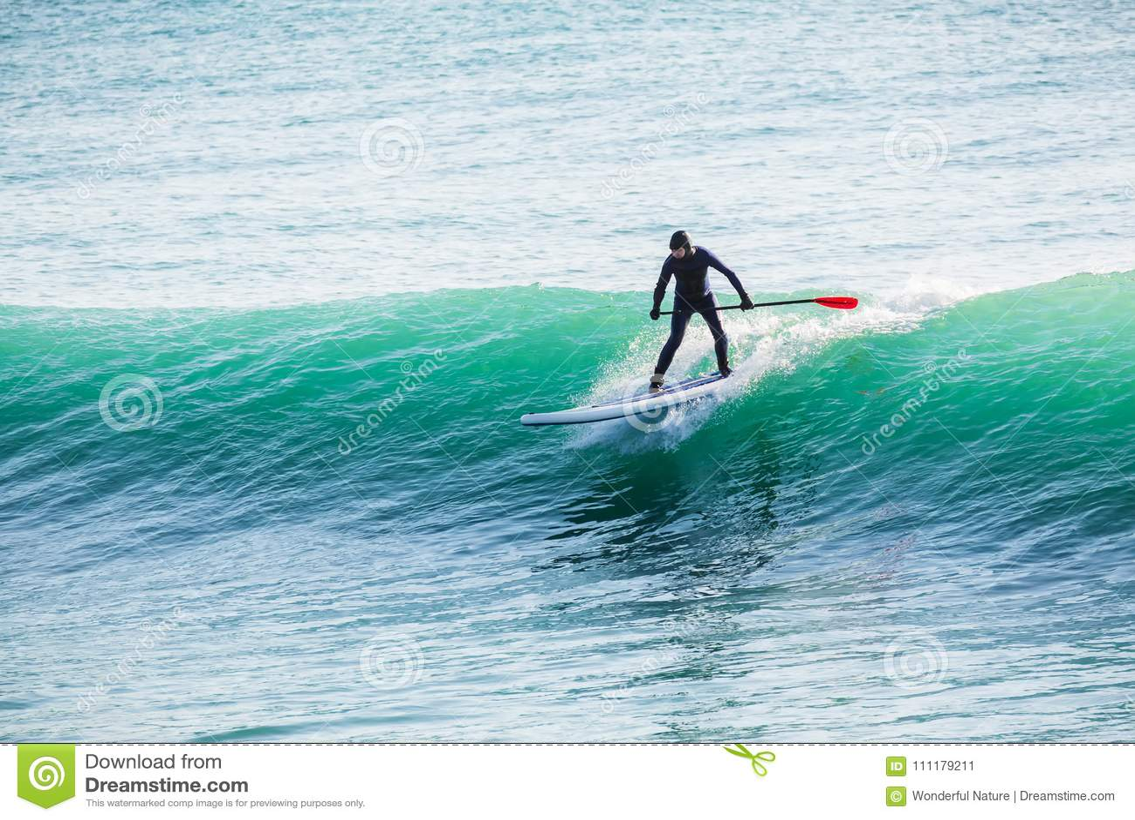 La persona que practica surf encendido se levanta el tablero de paleta en onda azul Paleta que practica surf en el océano