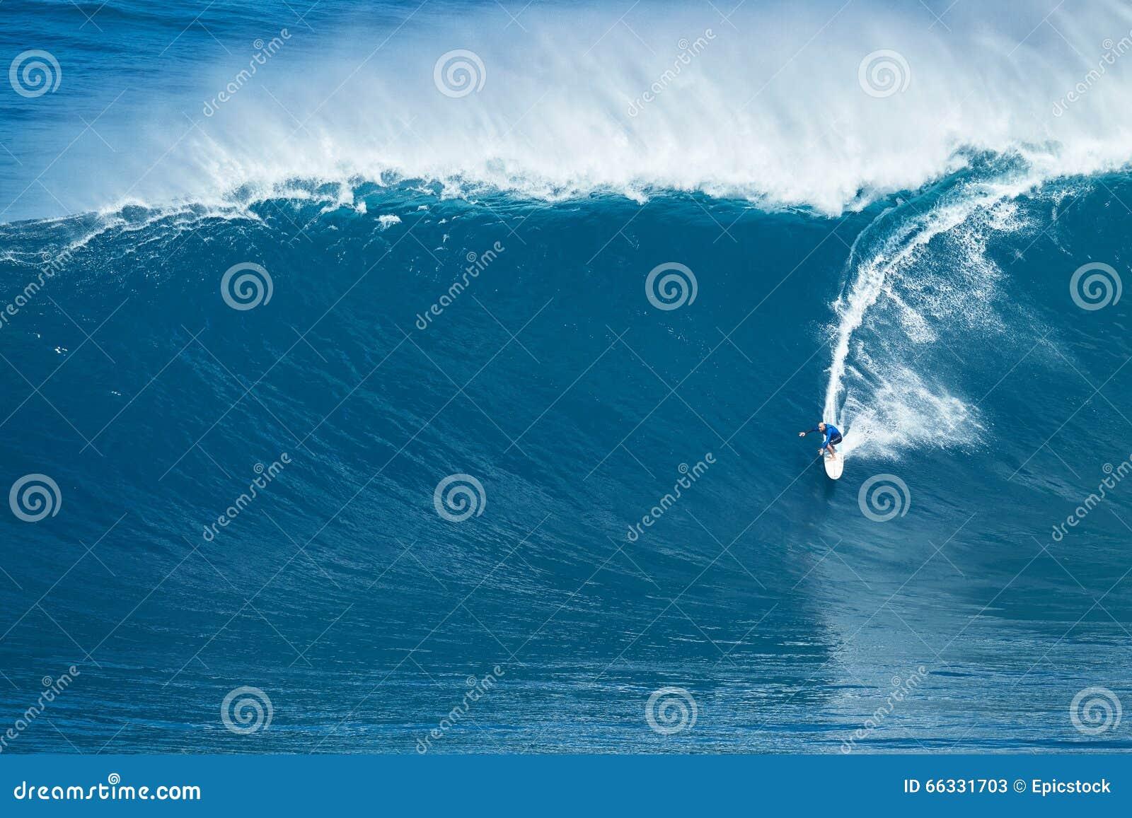 La persona que practica surf monta la onda gigante en los mandíbulas