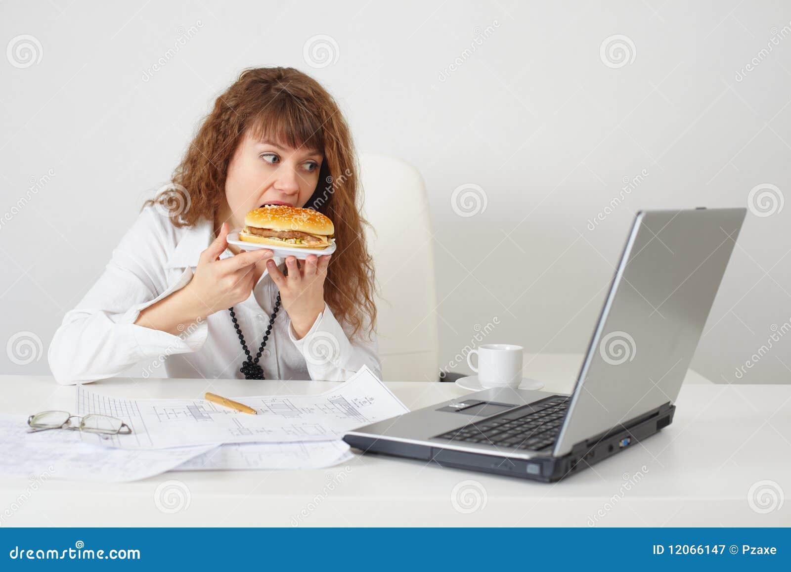 la personne au bureau sur le lieu de travail mange un hamburger image stock image 12066147. Black Bedroom Furniture Sets. Home Design Ideas