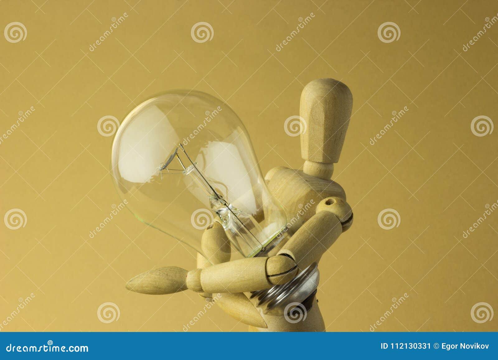 La personne en bois juge l ampoule électrique disponible