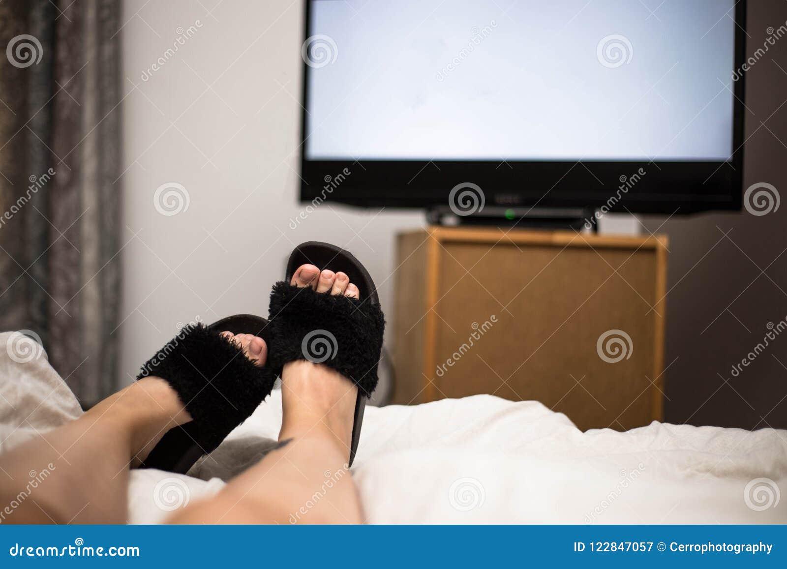 Tele Au Pied Du Lit la personne regarde la tv la nuit dans son lit avec ses