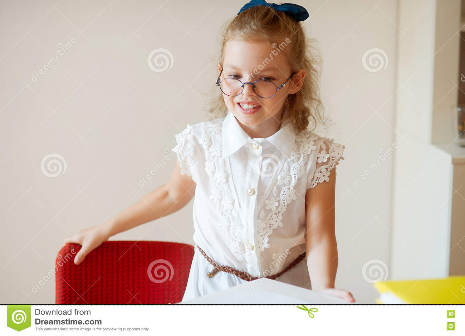 La petite écolière mignonne tient les bureaux proches
