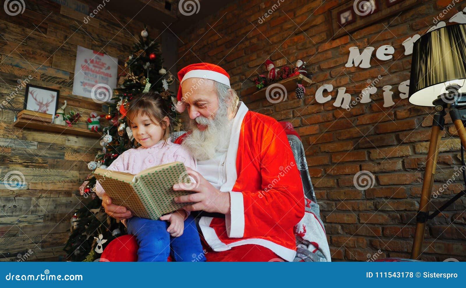 La petite fille étreint Santa et sourit heureusement r