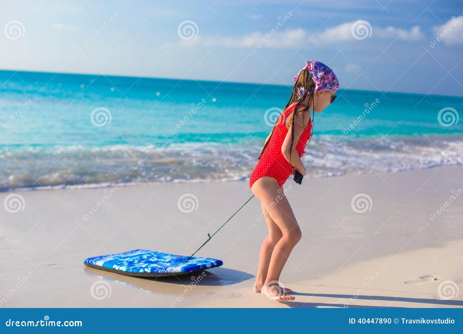 la petite fille adorable tire une planche de surf sur le rivage blanc photo stock image 40447890. Black Bedroom Furniture Sets. Home Design Ideas
