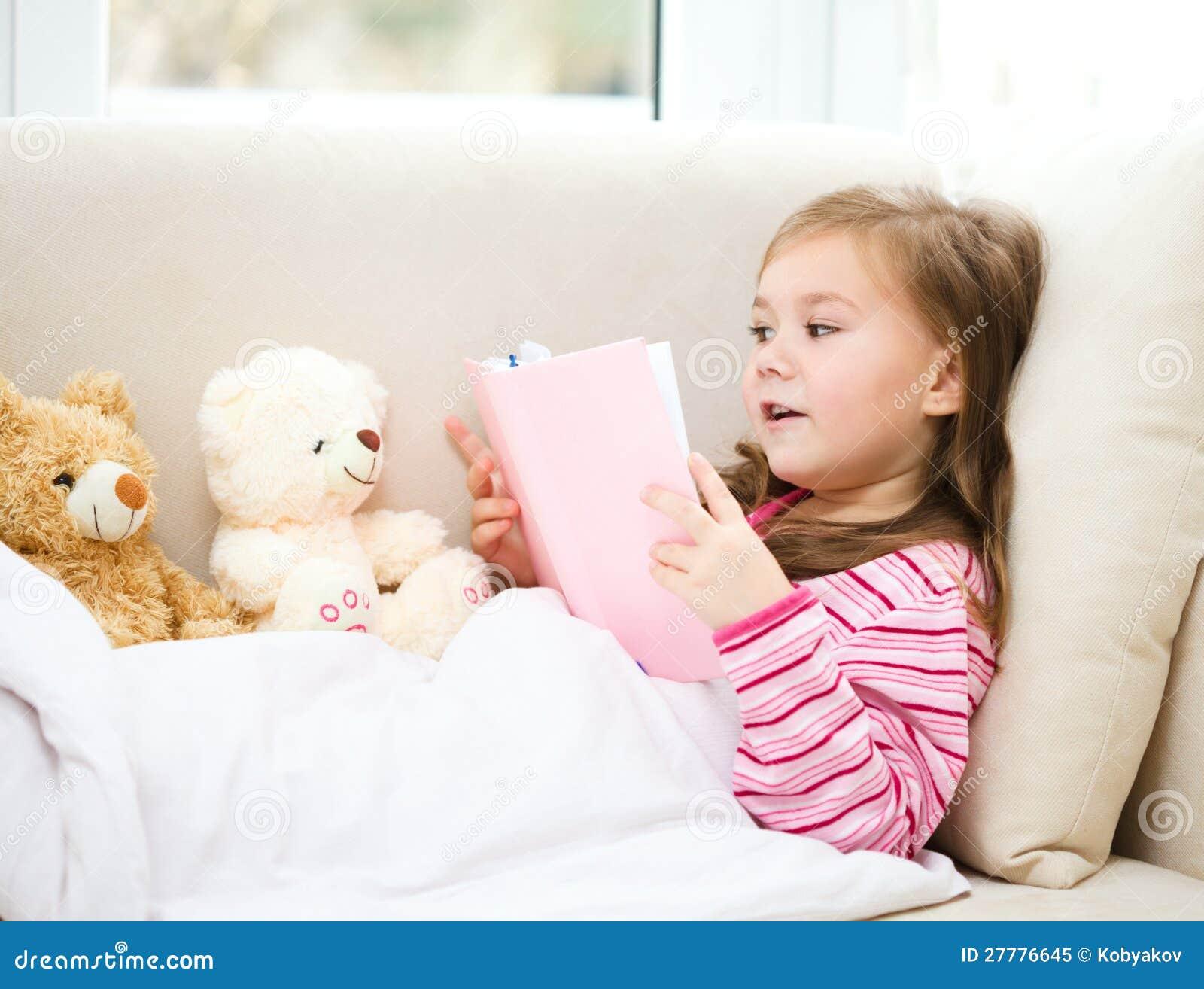 La petite fille affiche un livre pour ses ours de nounours