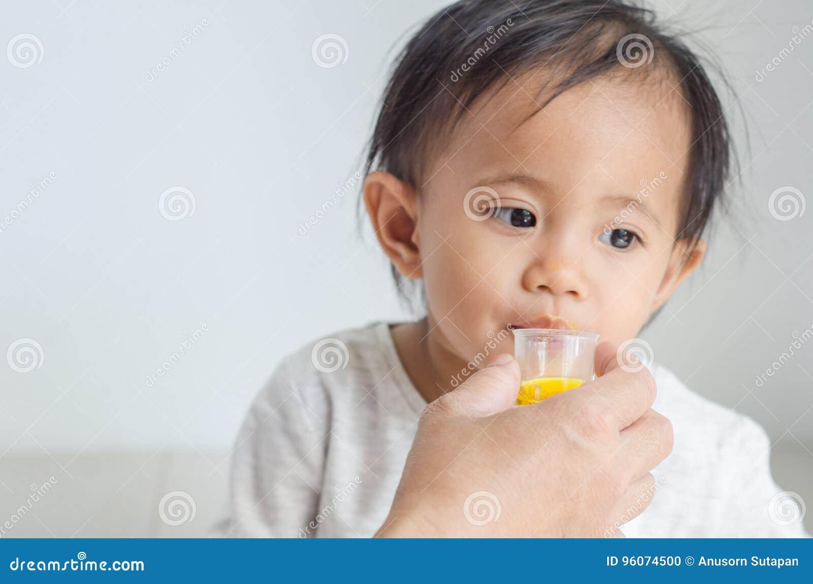 La petite fille asiatique prend le sirop de médecine avec sa mère