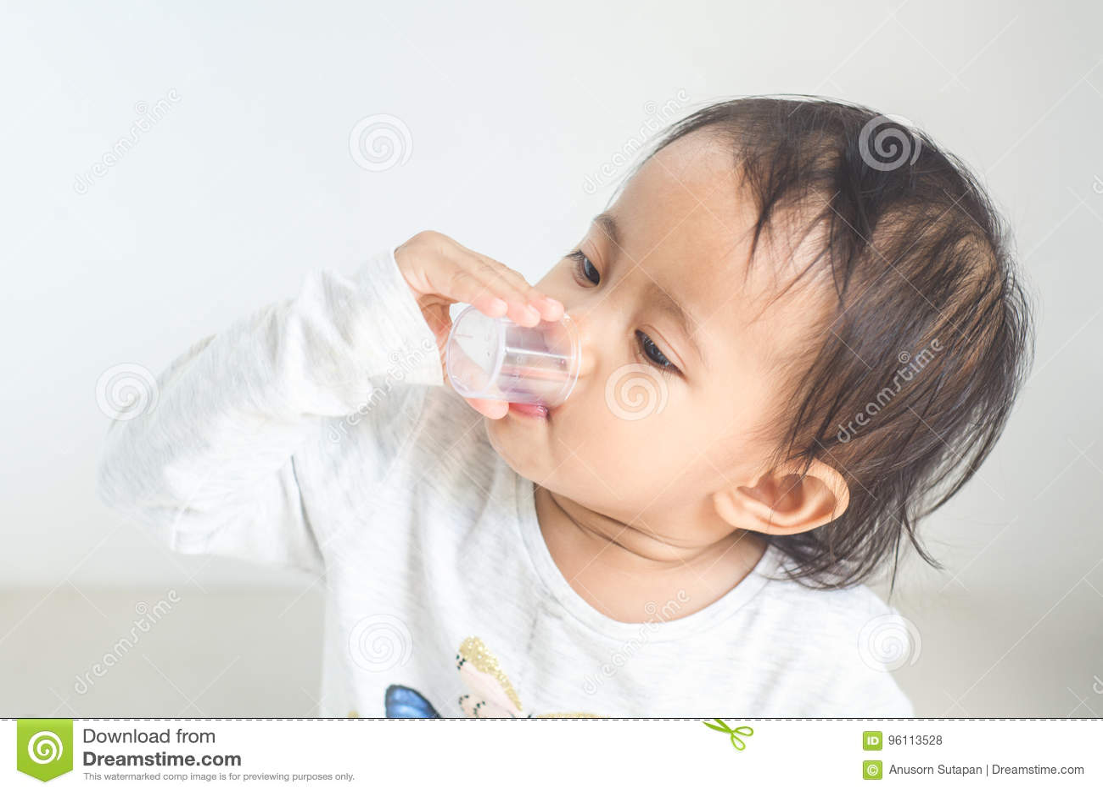 La petite fille asiatique prend le sirop de médecine seule
