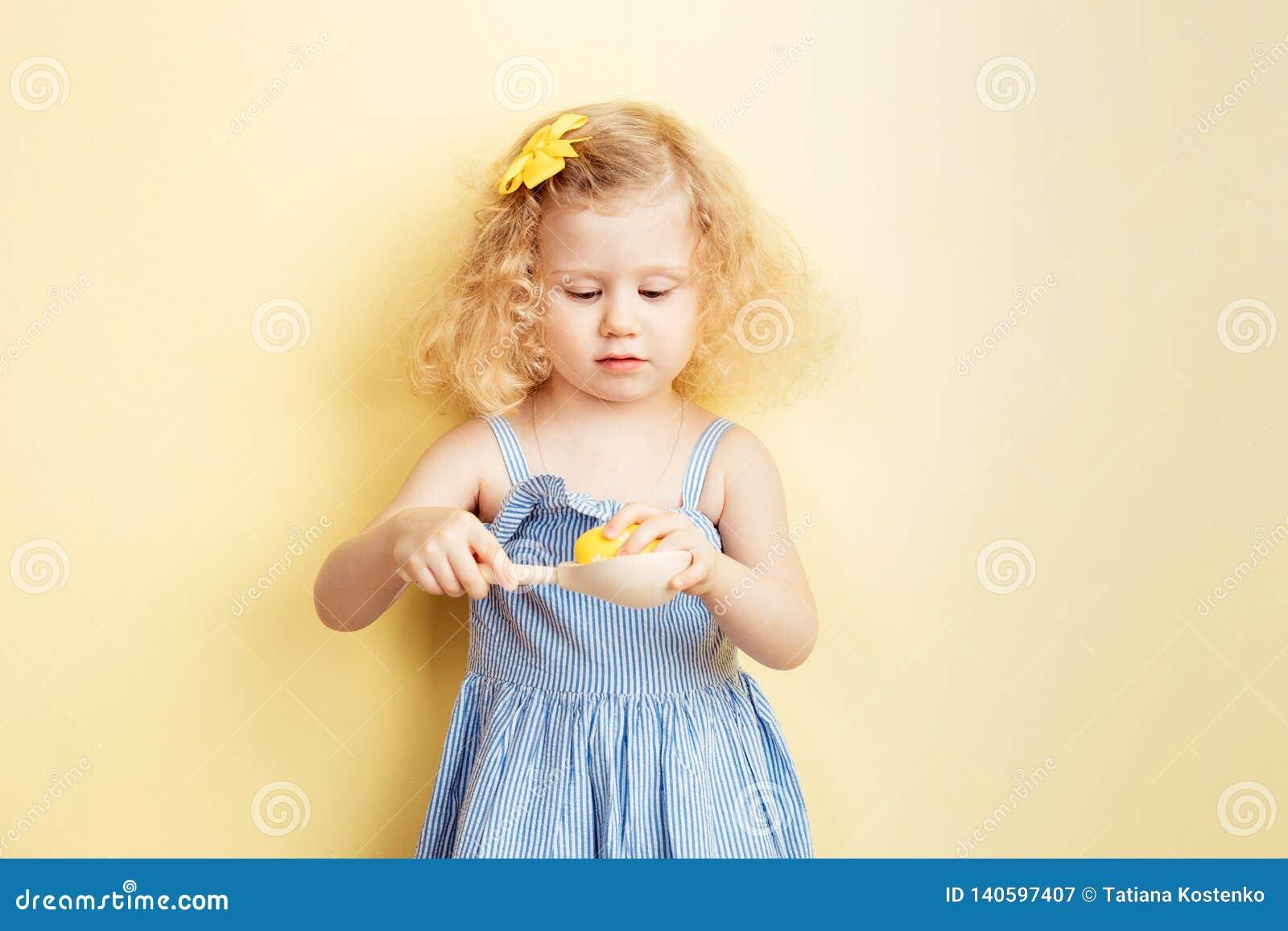 La petite fille bouclée de charme dans la robe bleu-clair tient une cuillère en bois avec un oeuf teint sur le fond du jaune