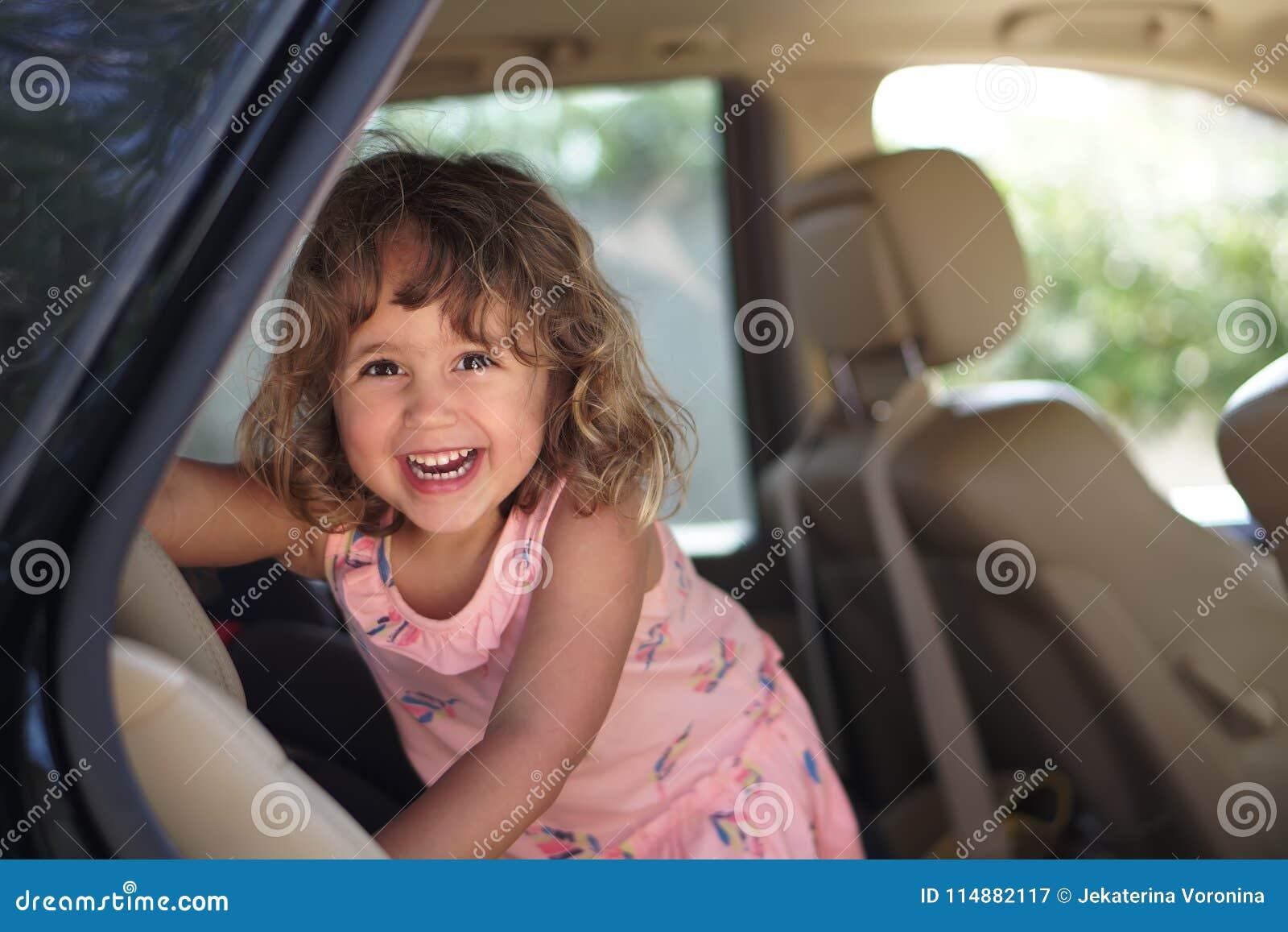 La petite fille d AUGURI semble heureuse dans la voiture