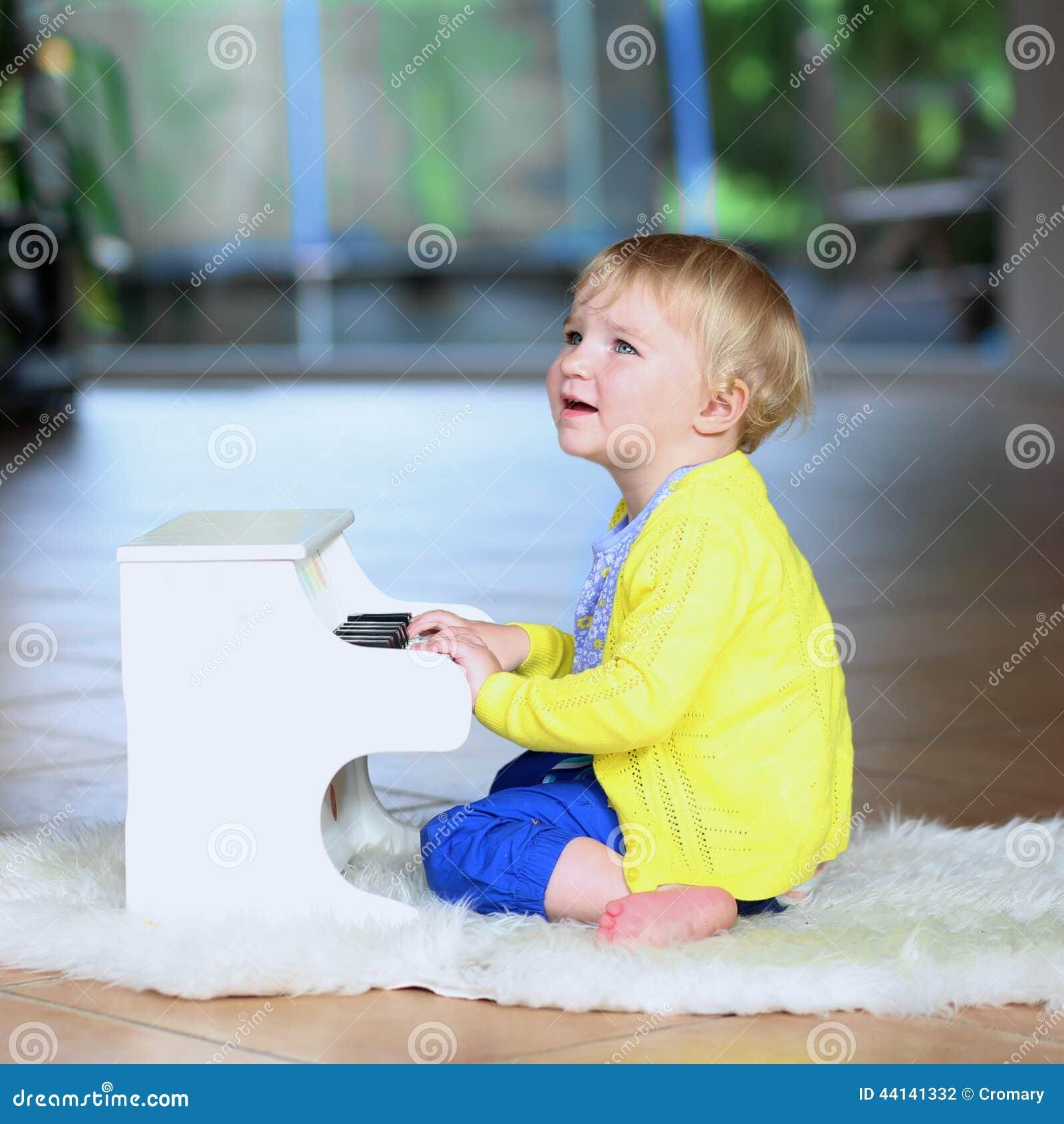 la petite fille d 39 enfant en bas ge joue le piano de jouet. Black Bedroom Furniture Sets. Home Design Ideas