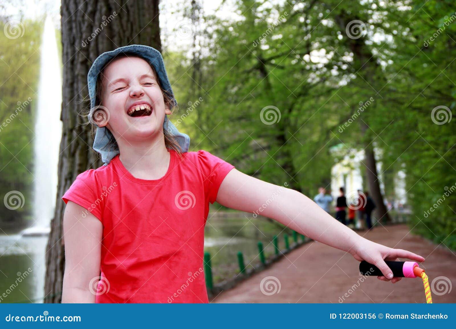 La petite fille dans des rires du Panama gaiement, fermant ses yeux avec plaisir, sur la rue