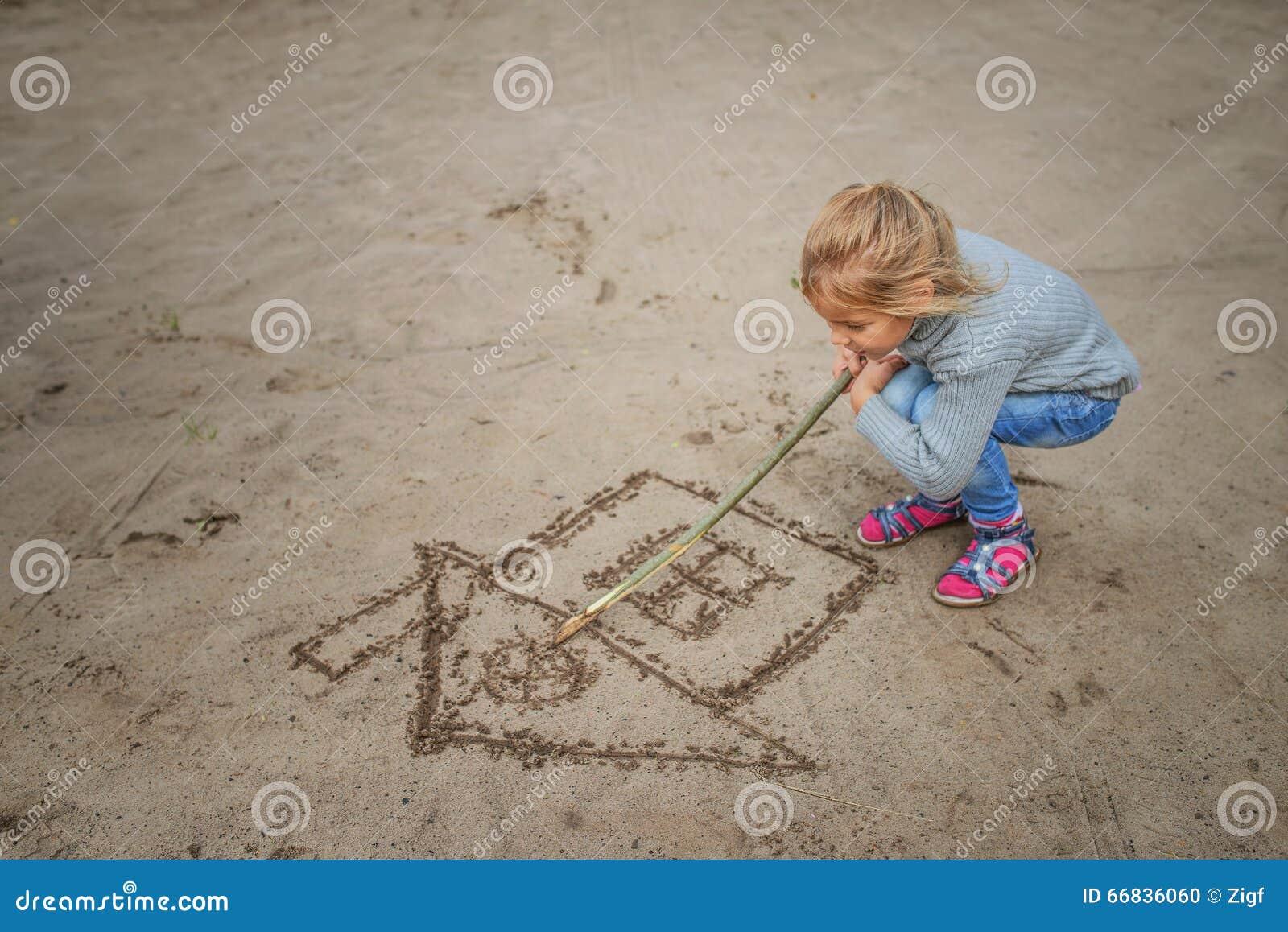 La petite fille dessine dans le sable