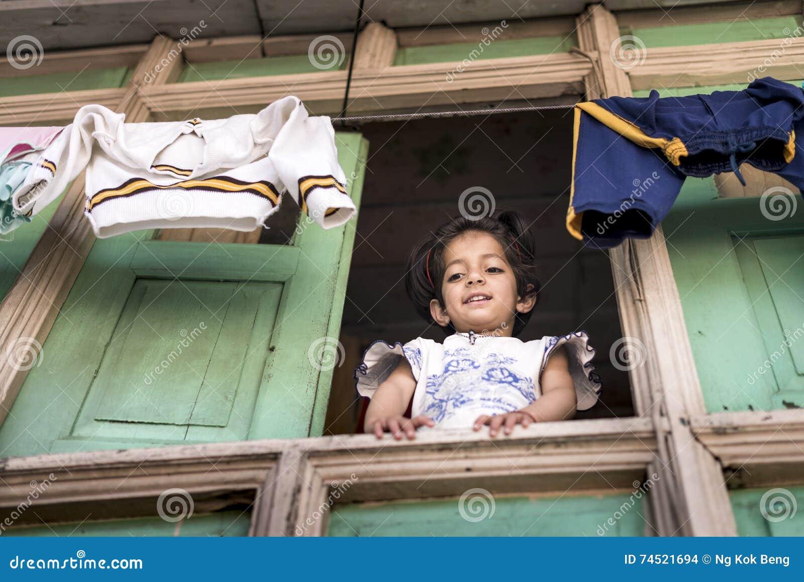 La petite fille douce regardent fixement vers le bas de sa fenêtre en bois de maison avec les vêtements accrochants en haut