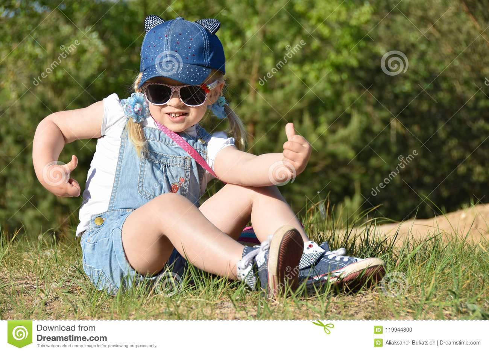 La petite fille est jouante et riante sur la pelouse verte en été