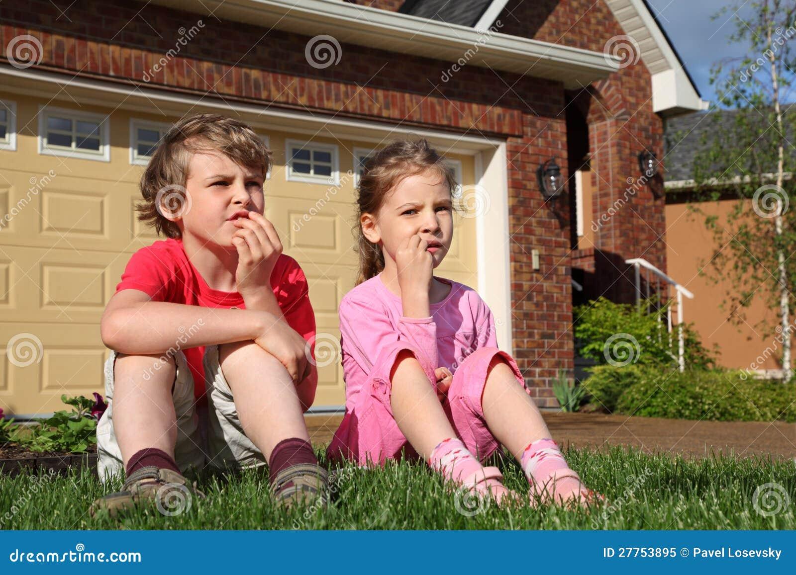 La petite fille et le garçon s assied sur l herbe près de la maison