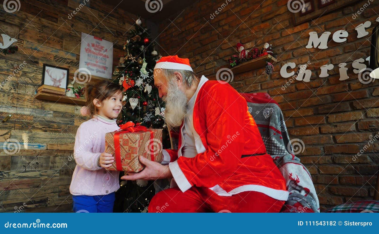 La petite fille européenne chuchote sur le souhait de Noël du ` s de Santa r