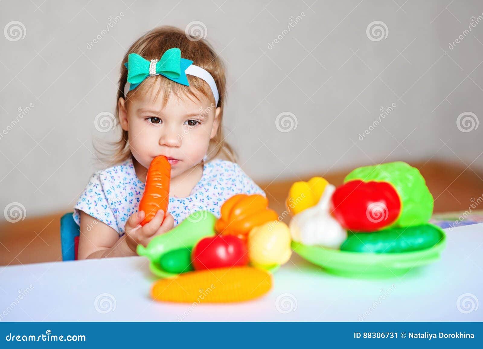 La petite fille joue à la table avec des légumes Végétarien d enfant Concept de la consommation saine