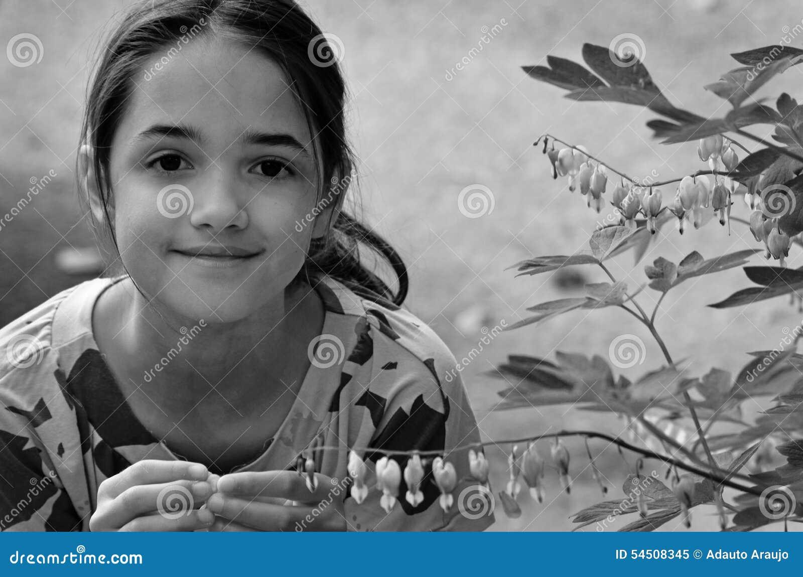 La petite fille joue avec des fleurs dans un jardin