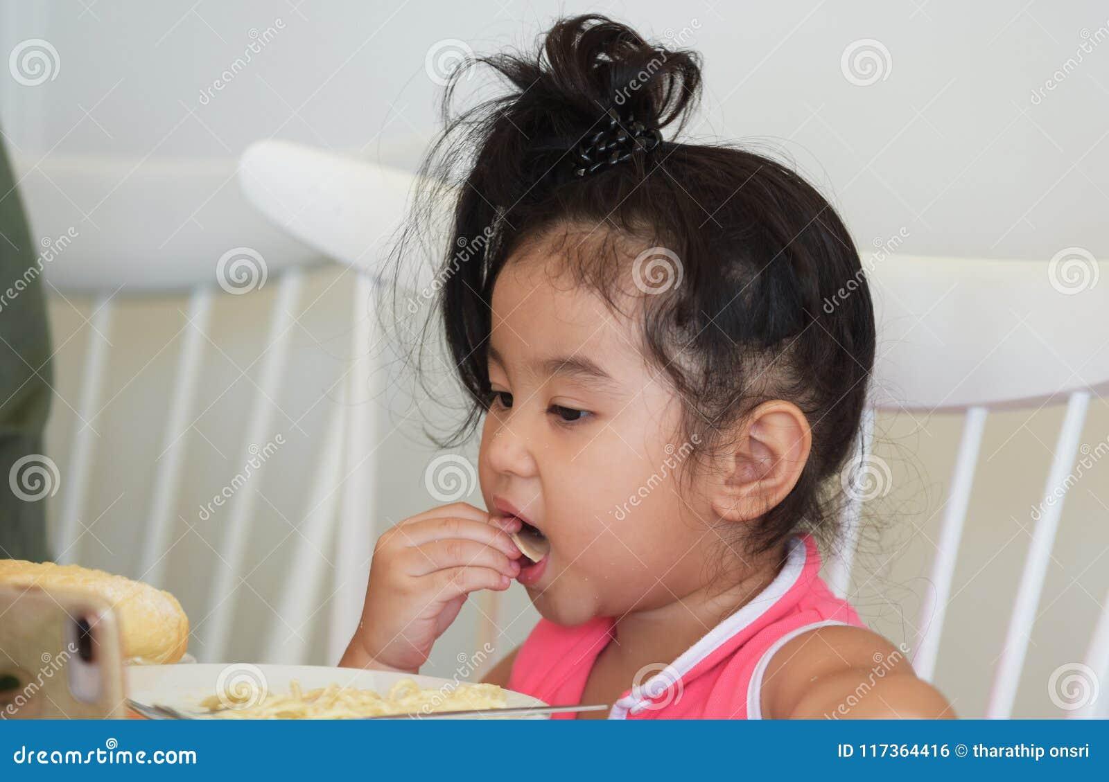 La petite fille mange de la nourriture délicieuse