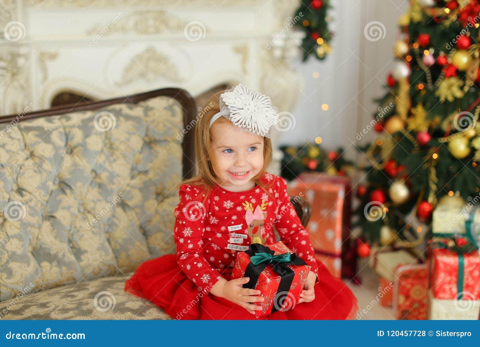 La petite fille portant la robe rouge, gardant le cadeau et s asseyant sur le sofa près a décoré la cheminée