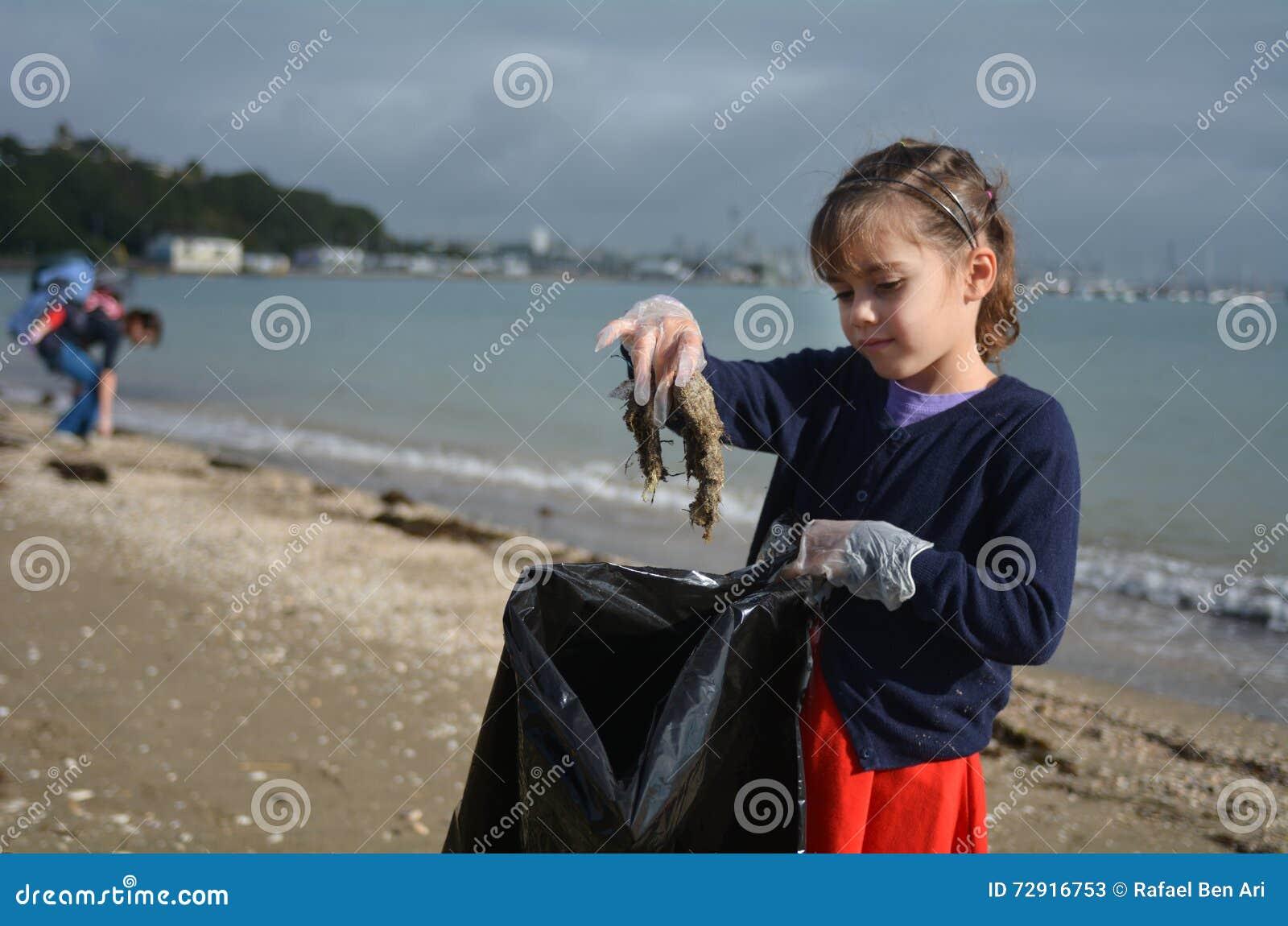 La petite fille prennent des déchets de la plage