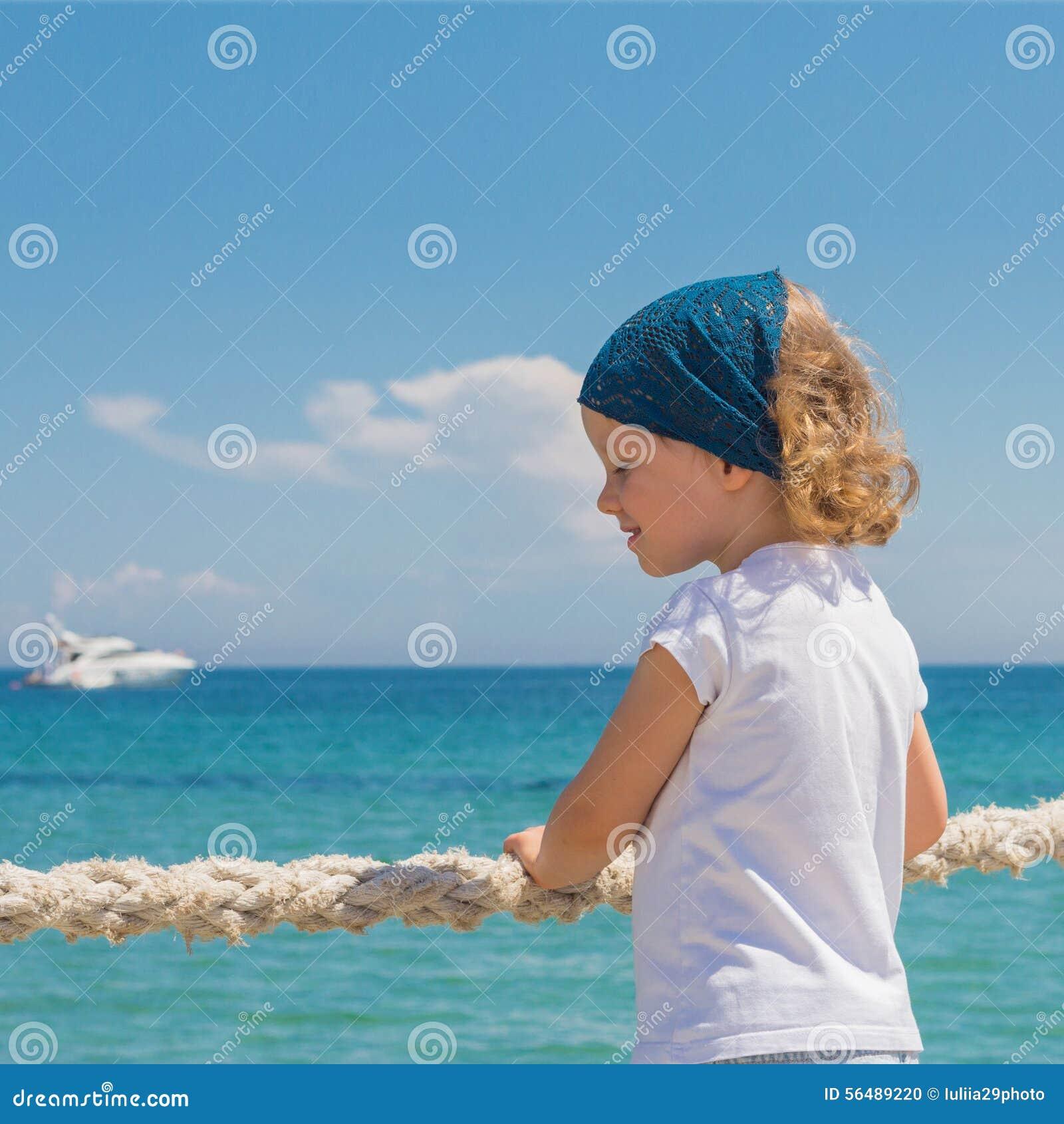 La petite fille regarde à la mer