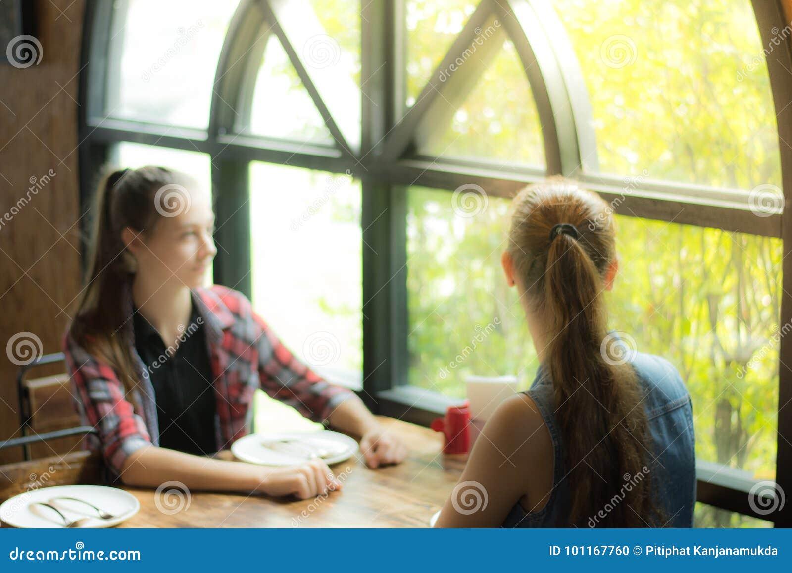 La photo a brouillé pour la jeune femme du fond deux s asseyant à la table attendant son repas Fille de sourire regardant hors de