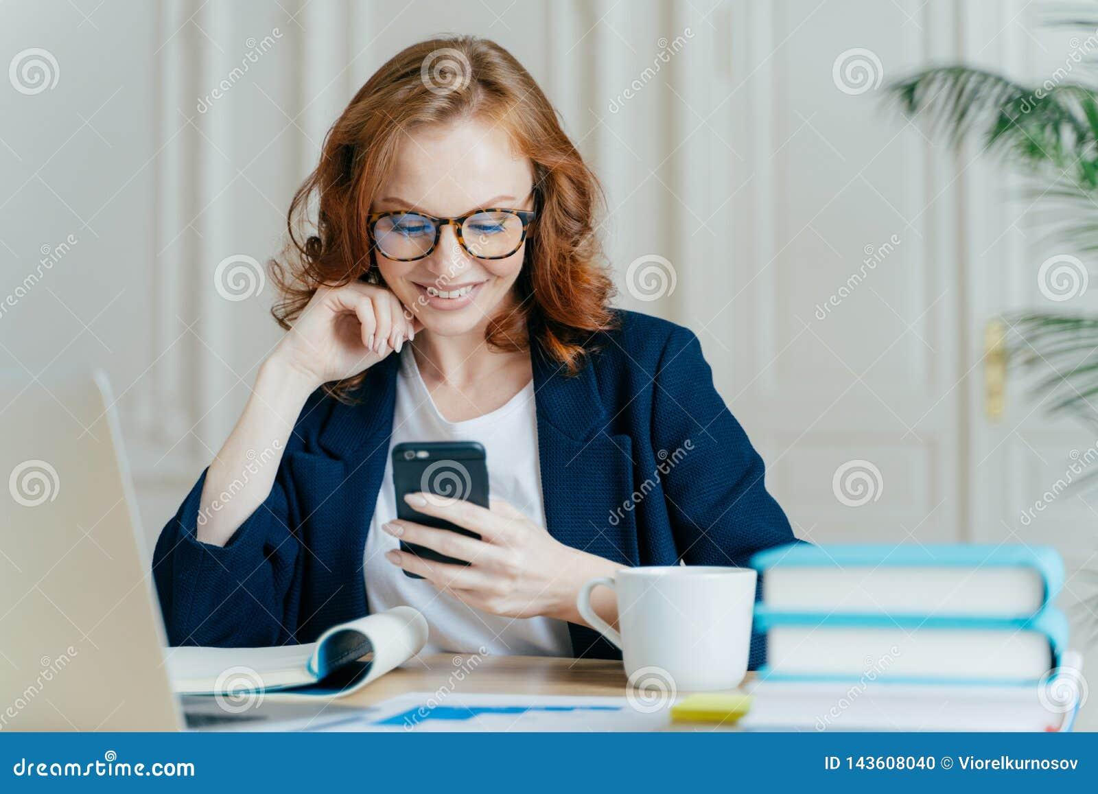 La photo de la belle femelle se repose avec le dispositif de smartphone, types retour, travaille dans le bureau sur l ordinateur