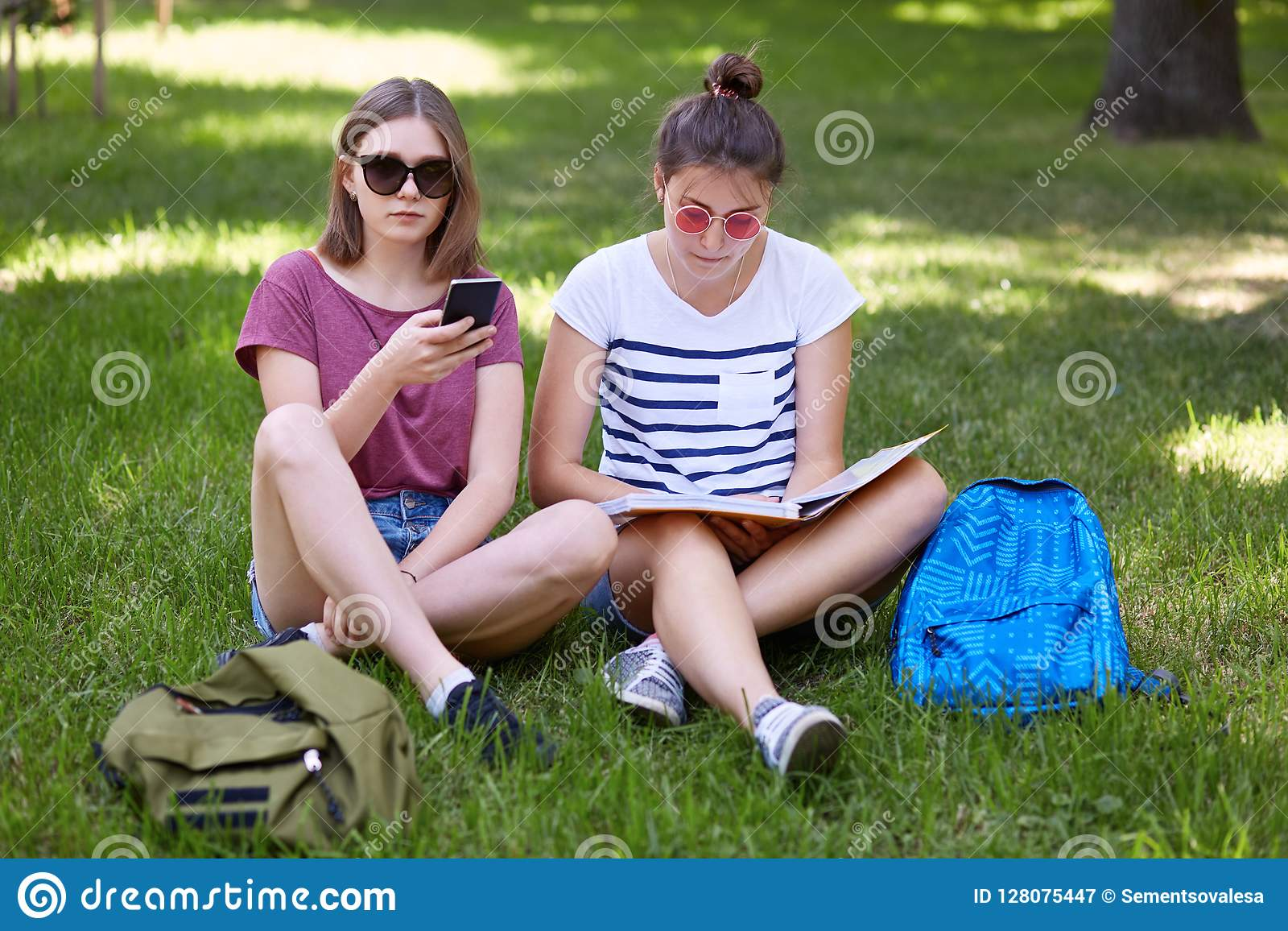 La photo de deux adolescents féminins se reposent sur l herbe verte extérieure, ont lu le livre et utilisent le téléphone portabl