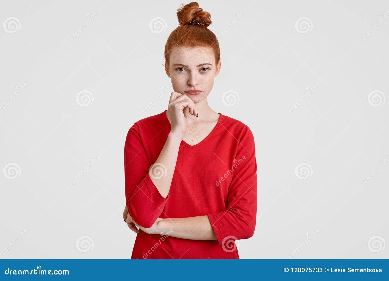 La photo de la femme sérieuse avec les cheveux rouges peignés en petit pain, menton de prises, maintient des mains en partie croi