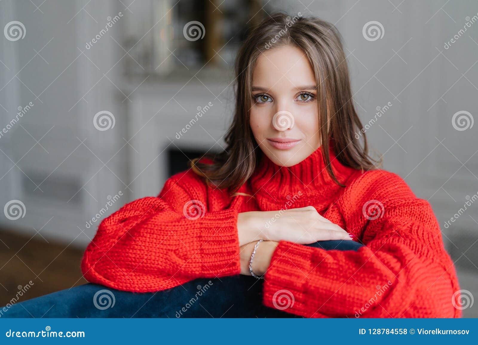 La photo de la jeune bonne femme de brune de lookng apprécie le jour de congé à la maison, a le regard sérieux à l appareil-photo