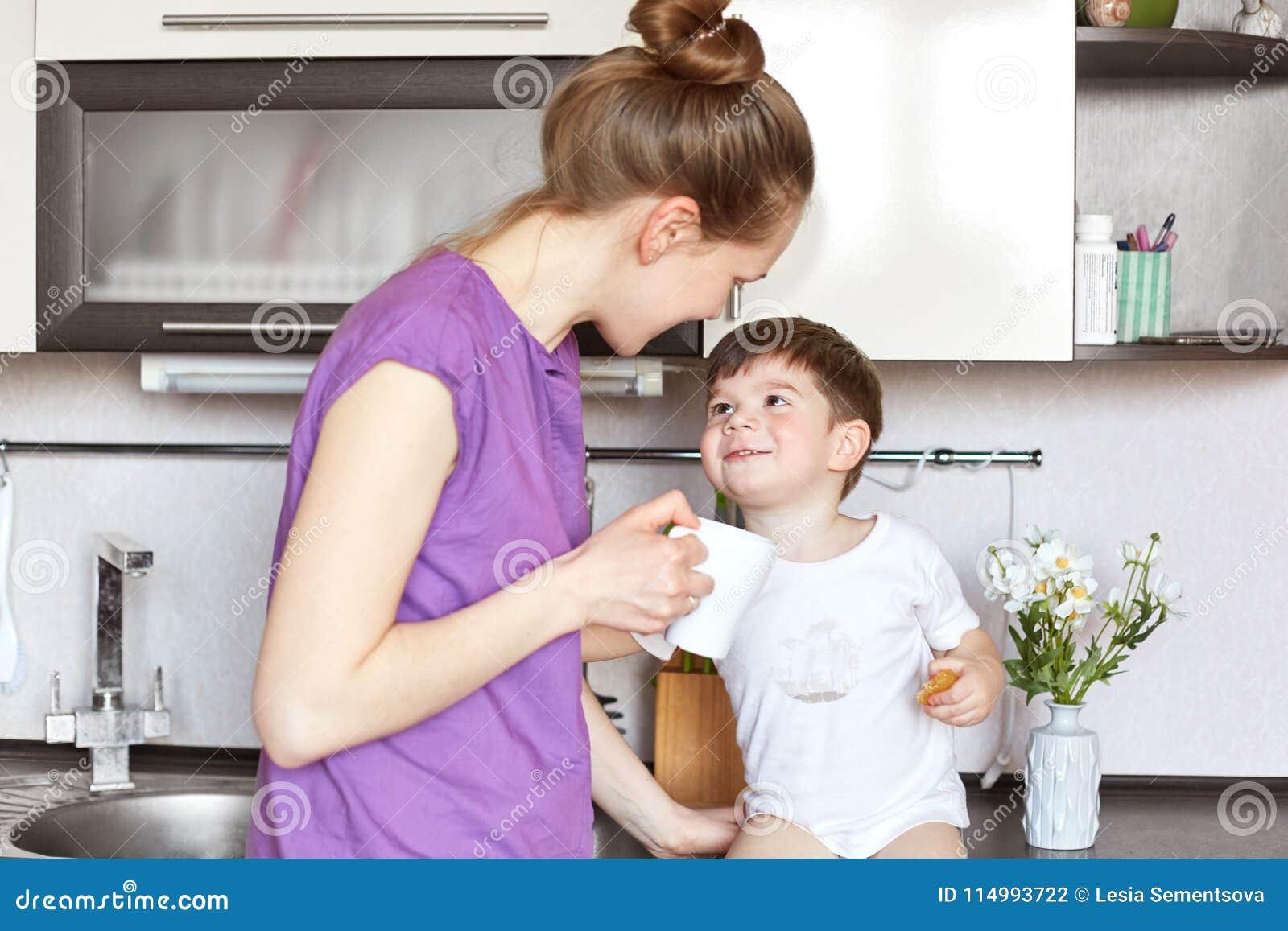 La photo de la jeune femme dans les vêtements décontractés se tient contre l intérieur de cuisine, regarde son fils adorable avec