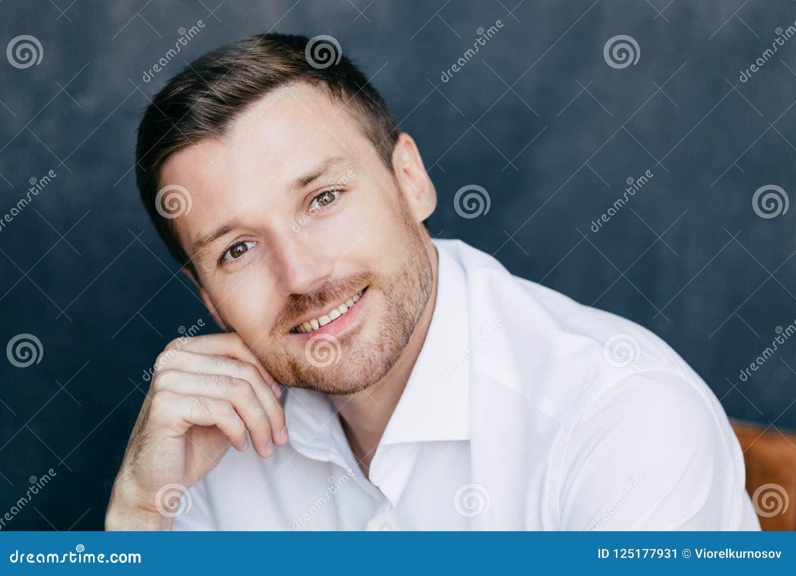 La photo du jeune entrepreneur masculin avec le poil, maintient la main sur la joue, habillée dans la chemise blanche élégante, d