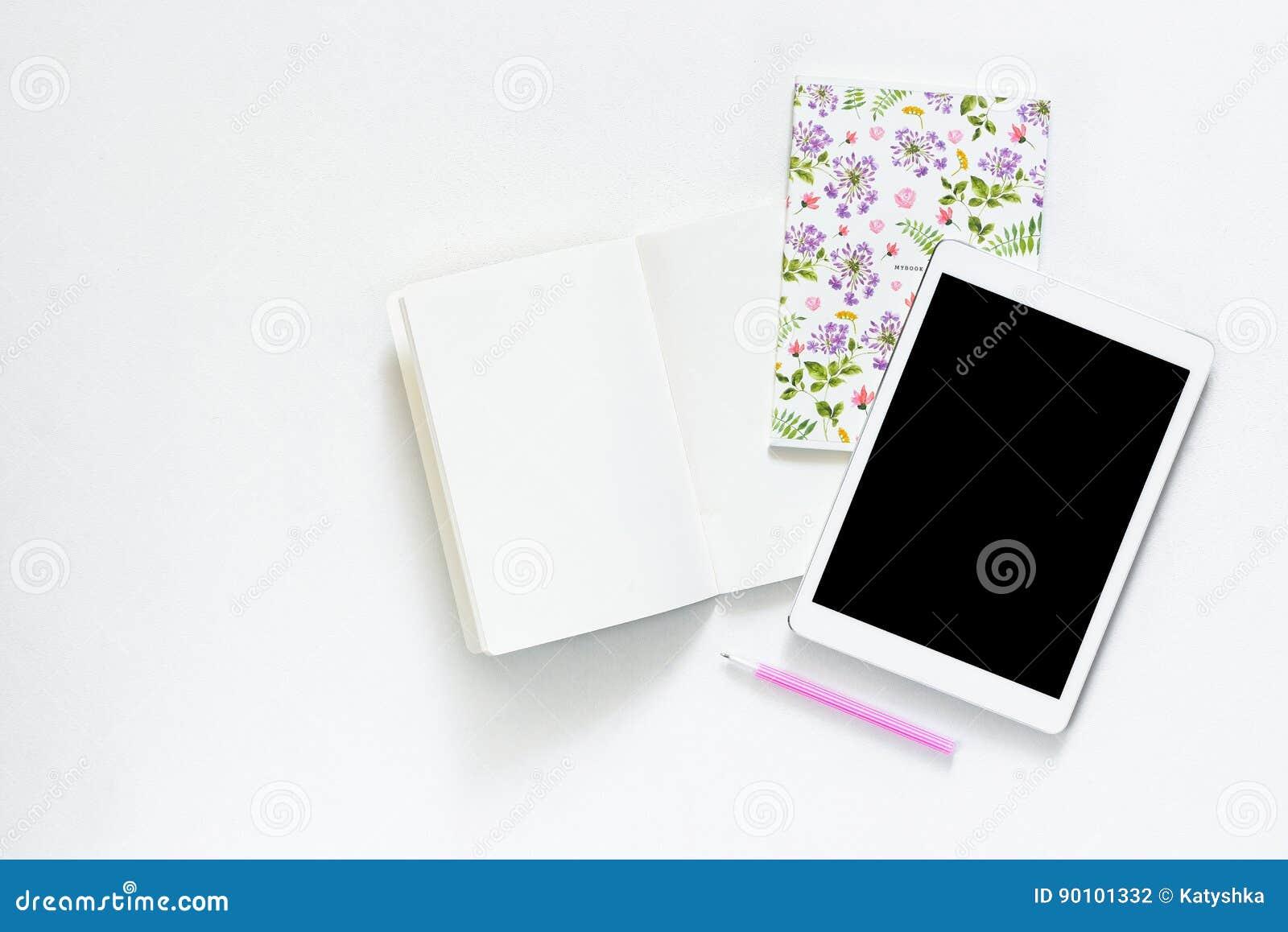 La photo plate de configuration du bureau blanc de bureau avec le comprimé et le carnet ouvert copient le fond de l espace