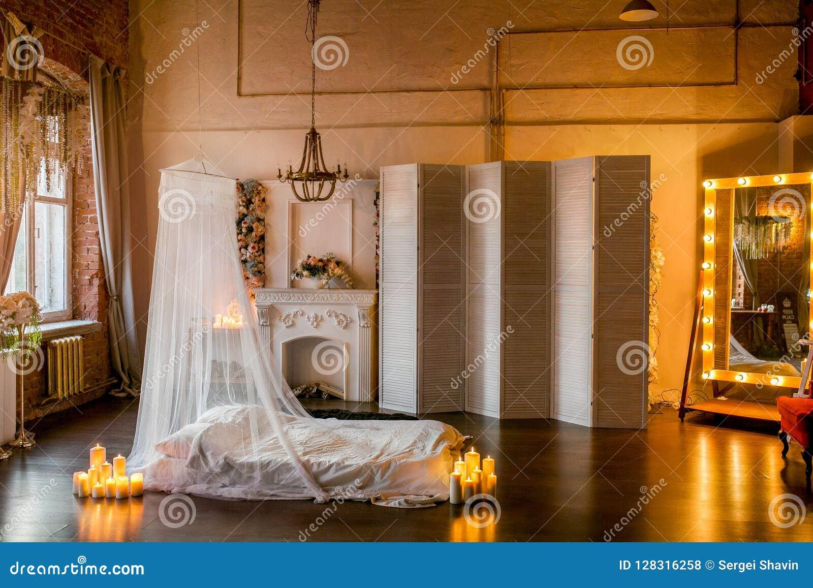 La pièce de style du grenier avec un lit, un auvent, une cheminée blanche avec une composition florale, un écran blanc, un grand