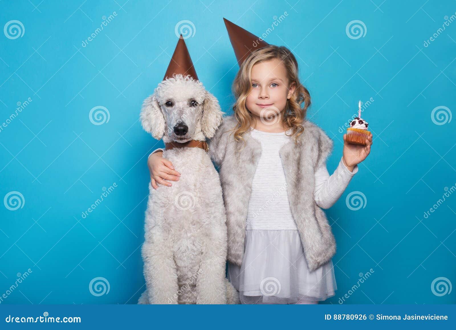 La piccola bella ragazza con il cane celebra il compleanno Amicizia Amore Torta con la candela Ritratto dello studio sopra fondo