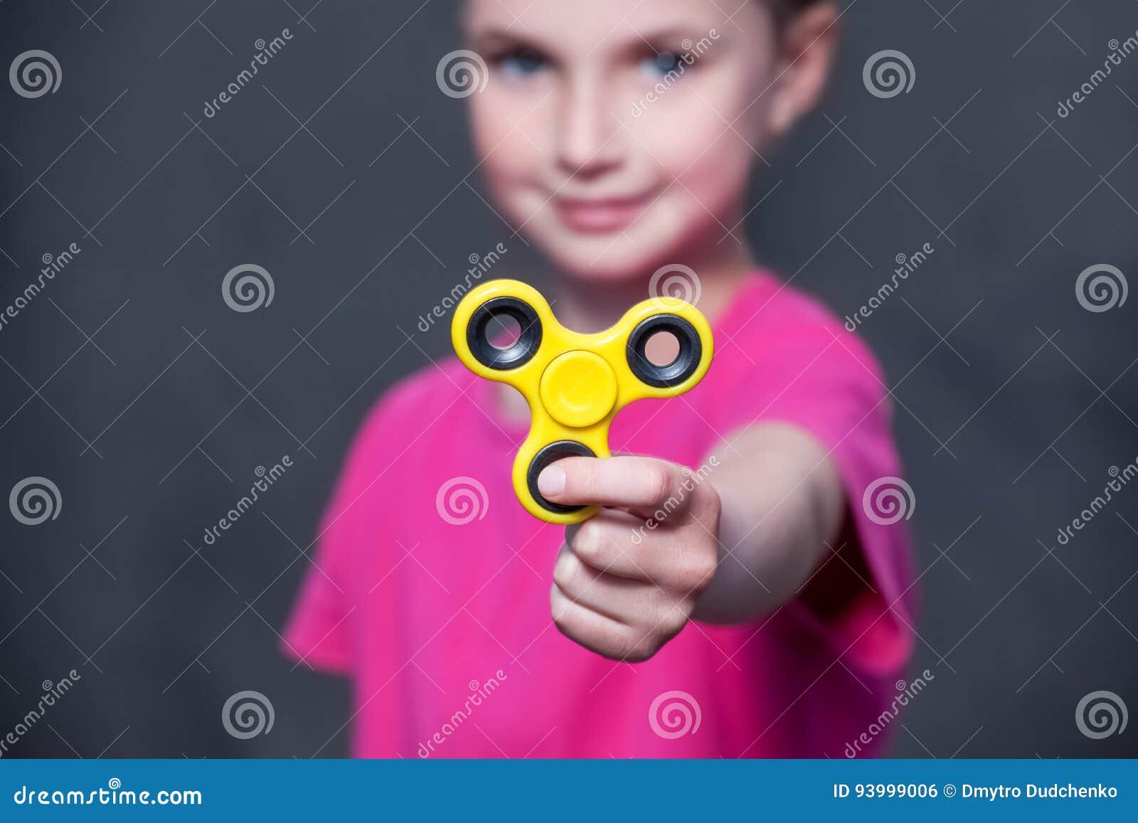 La piccola bella ragazza in maglietta rosa sta giocando il filatore giallo a disposizione