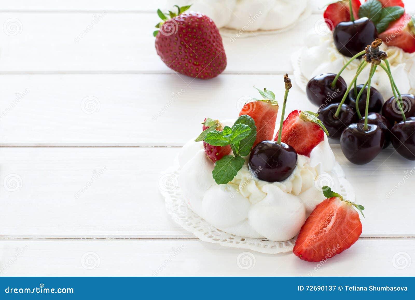 La piccola meringa casalinga di pavlova agglutina con la crema di mascarpone, le fragole, le ciliege e le foglie di menta fresca