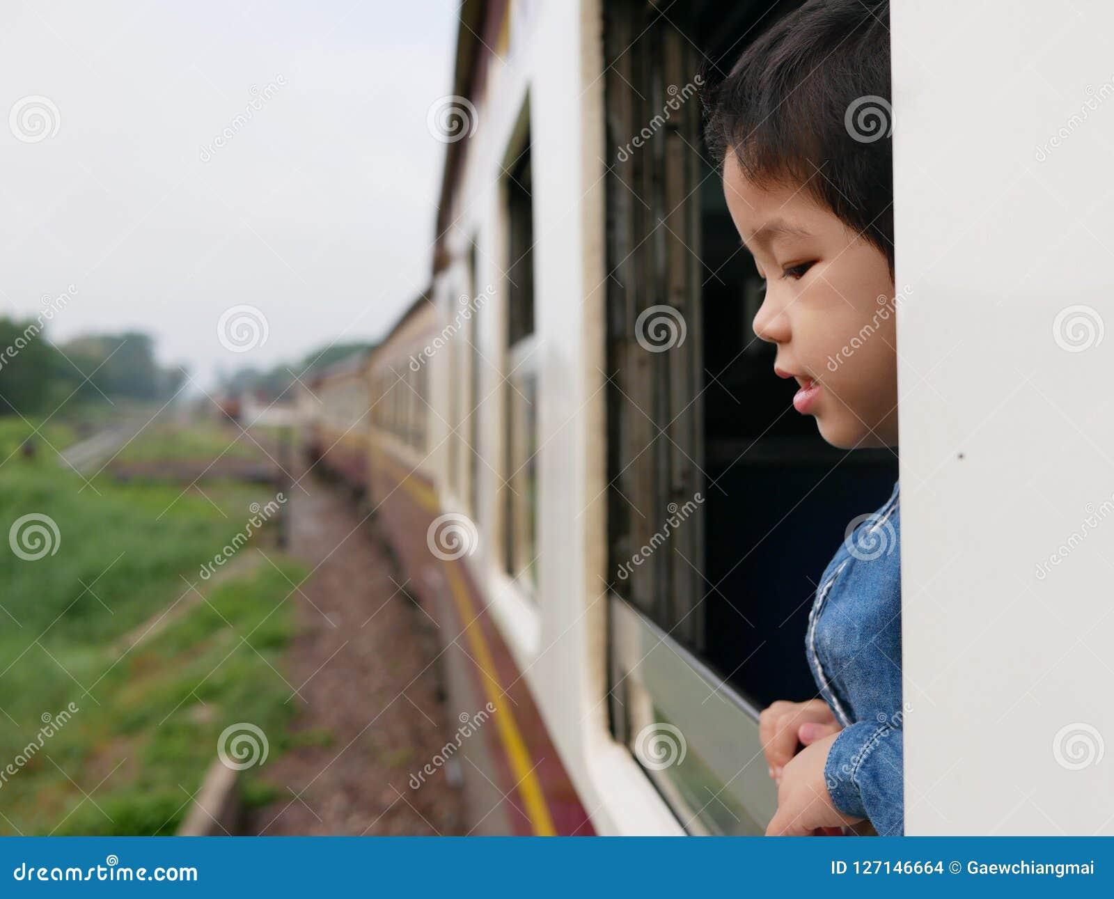 La piccola neonata asiatica gode di di attaccare la sua testa da una finestra del treno e di avere le fruste del vento contro il