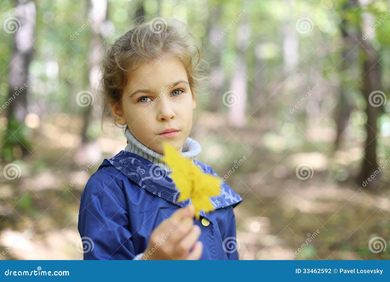La piccola ragazza caucasica triste tiene la foglia e guarda